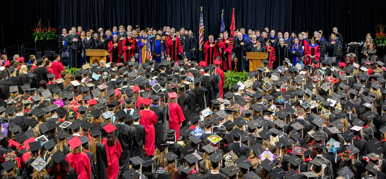 2018 Commencement ceremonies with students walking to podium wearing red and black regalia.