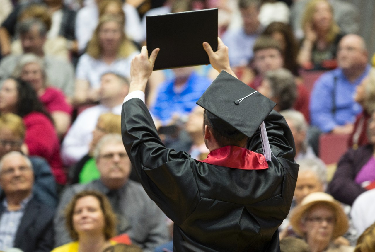 Student holds grad certificate in front of crowd at UC Commencement ceremony.