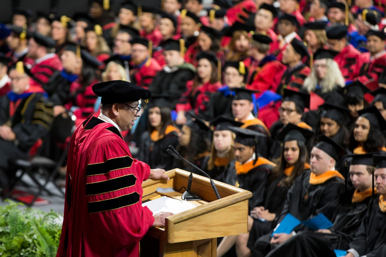 UC's President Neville Pinto speaks at the podium during a UC Commencement ceremony.