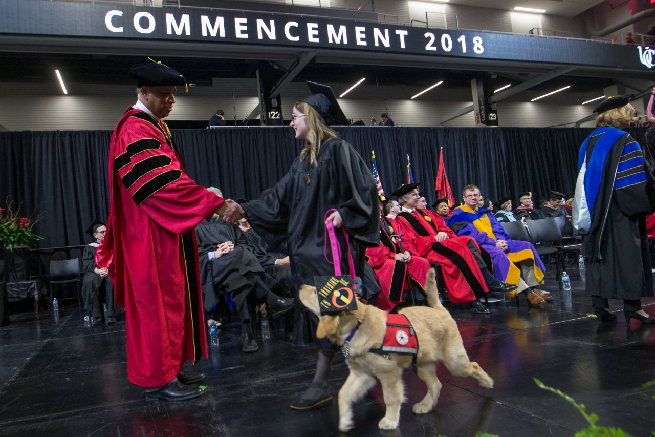A student receives her diploma holding her therapy dog on a leash during a UC Commencement ceremony.