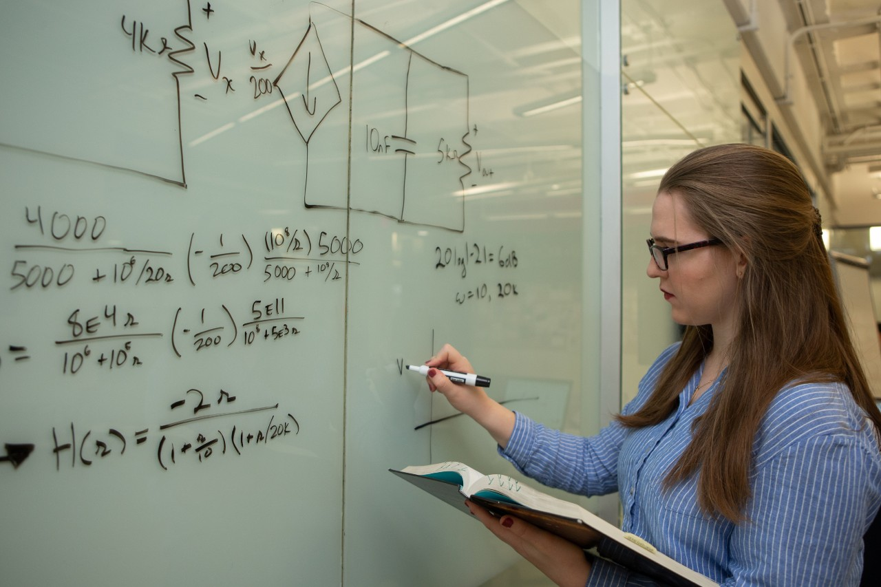 Laura Stegner solves electrical engineering problems on a white board.