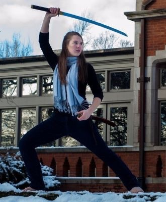 Laura Stegner raises her weapon during a martial arts pose as president of UC's club taekwondo team.