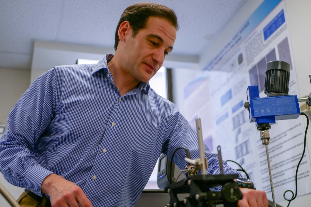 Simonetti stands over a piece of equipment in his lab.