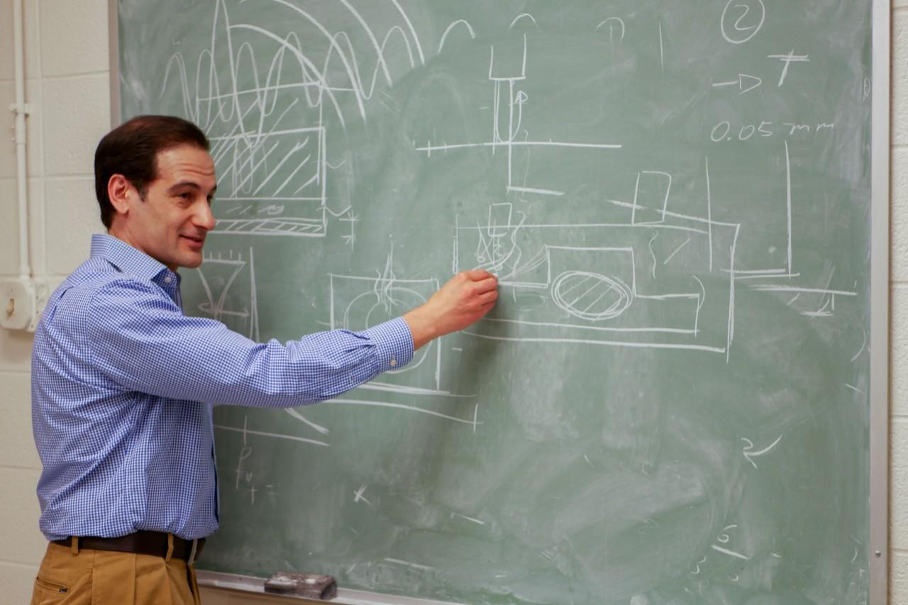 Francesco Simonetti stands at a blackboard diagramming a process in chalk.