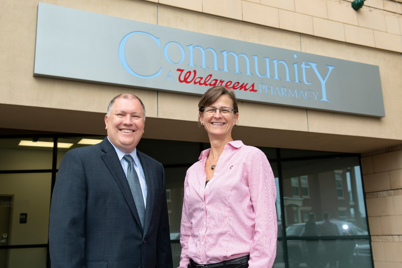 Representative of Walgreens representative Dan Hein and faculty member Bethanne Brown, PharmD, standing in front of the Walgreens Community Pharmacy