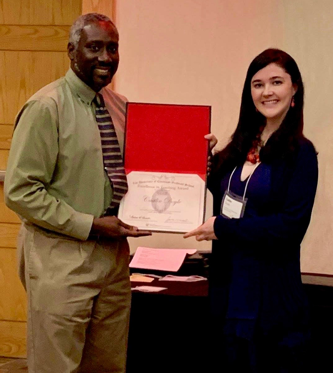 UC grad student Caitlin Doyle receives UC's Excellence in Teaching Award from a university representative.