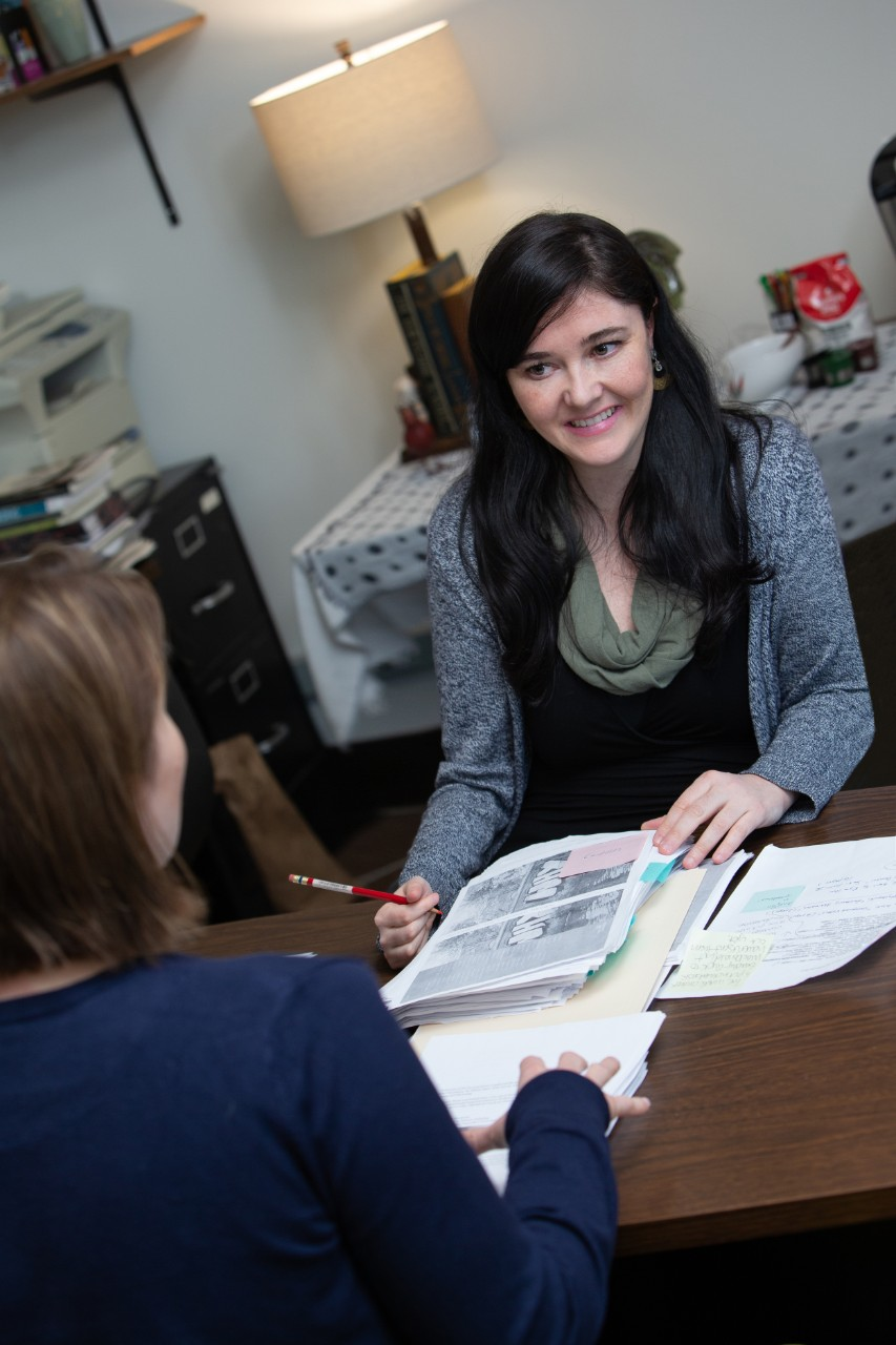 UC grad student Caitlin Doyle reviews scholarship applications at a table with another woman.