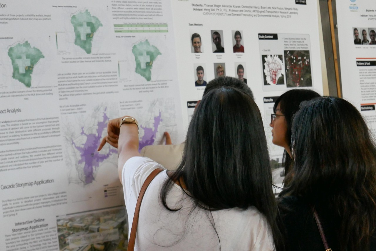students point to posters on wall