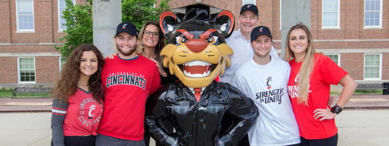 A family of six gathers around a statue of the UC Bearcat dressed in graduation clothing outside of McMicken Hall.