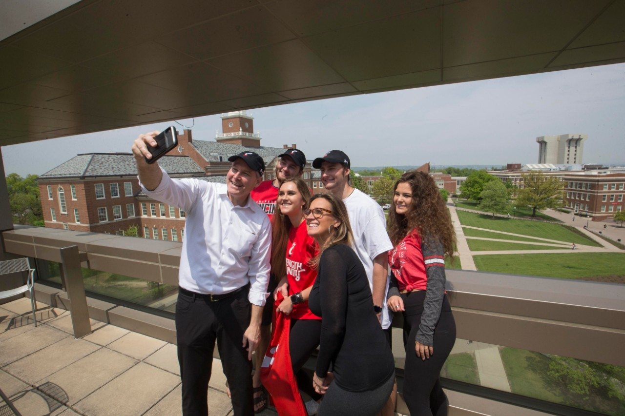 A family of six takes a selfie using a cell phone camera on a large terrace.