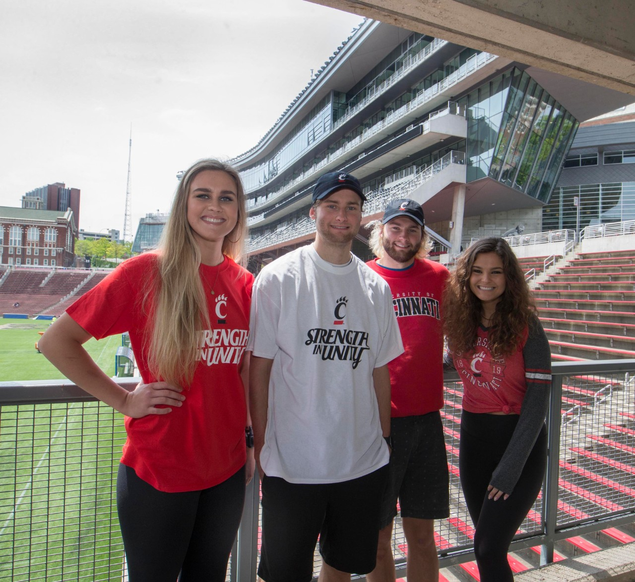 Two female and two male students stand in front of the press box at Nippert Stadium.