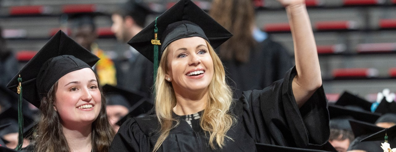 Students smile at Fifth Third Arena during commencement.