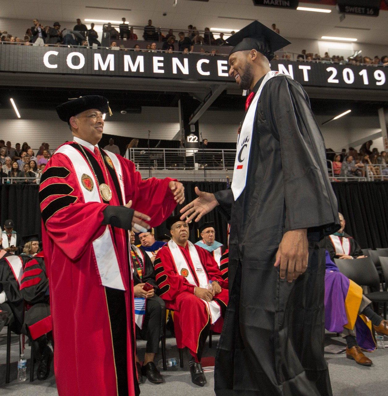 DerMarr Johnson shakes hands with Neville Pinto on stage at Fifth Third Arena.