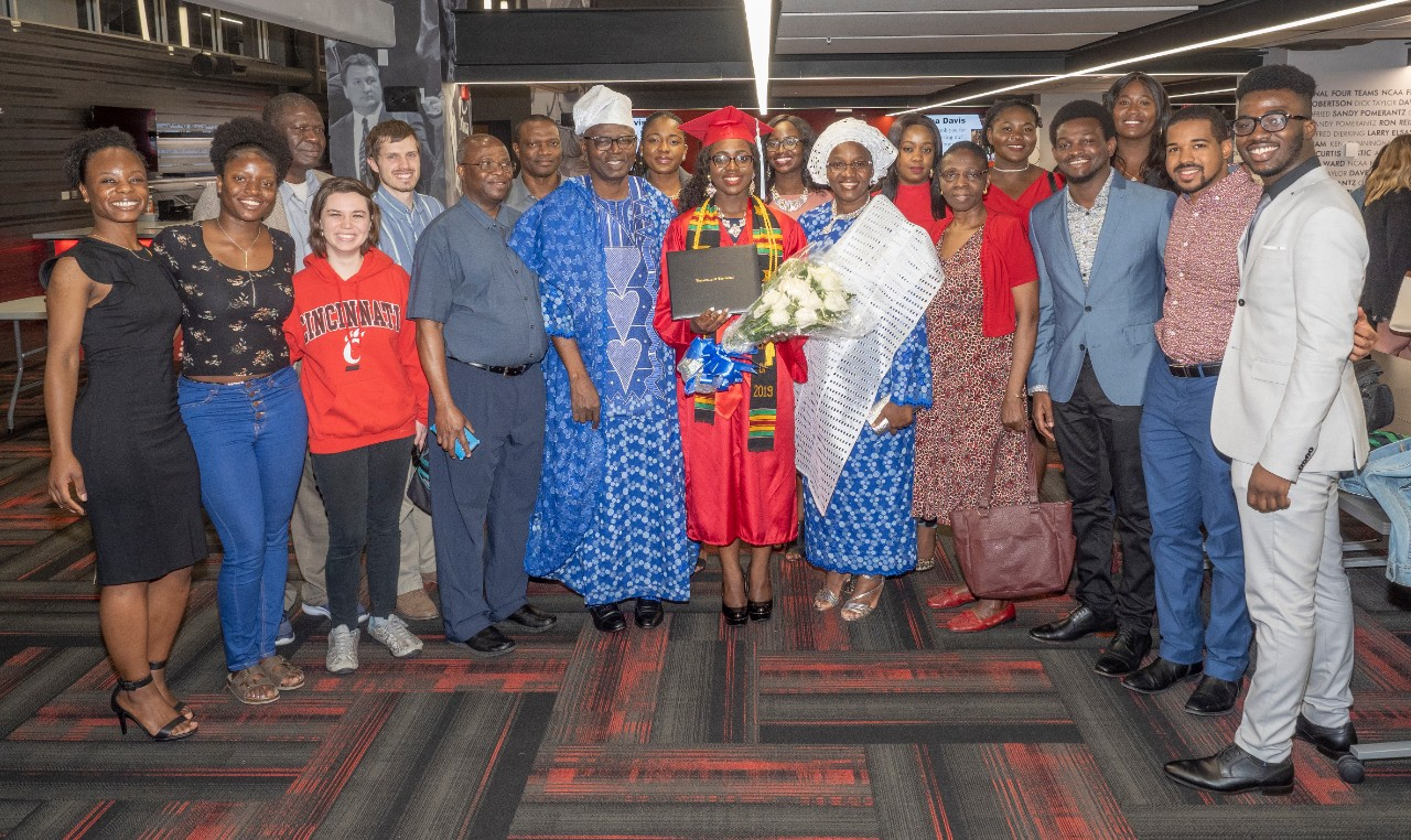 A family photo shows more than a dozen family members posing with a graduate.