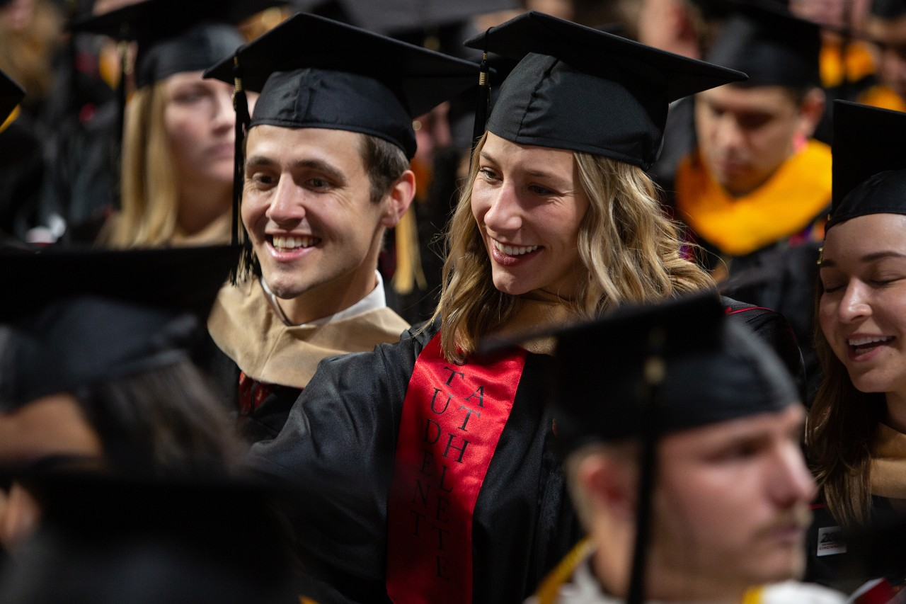 A group of students celebrates in their caps and gowns.