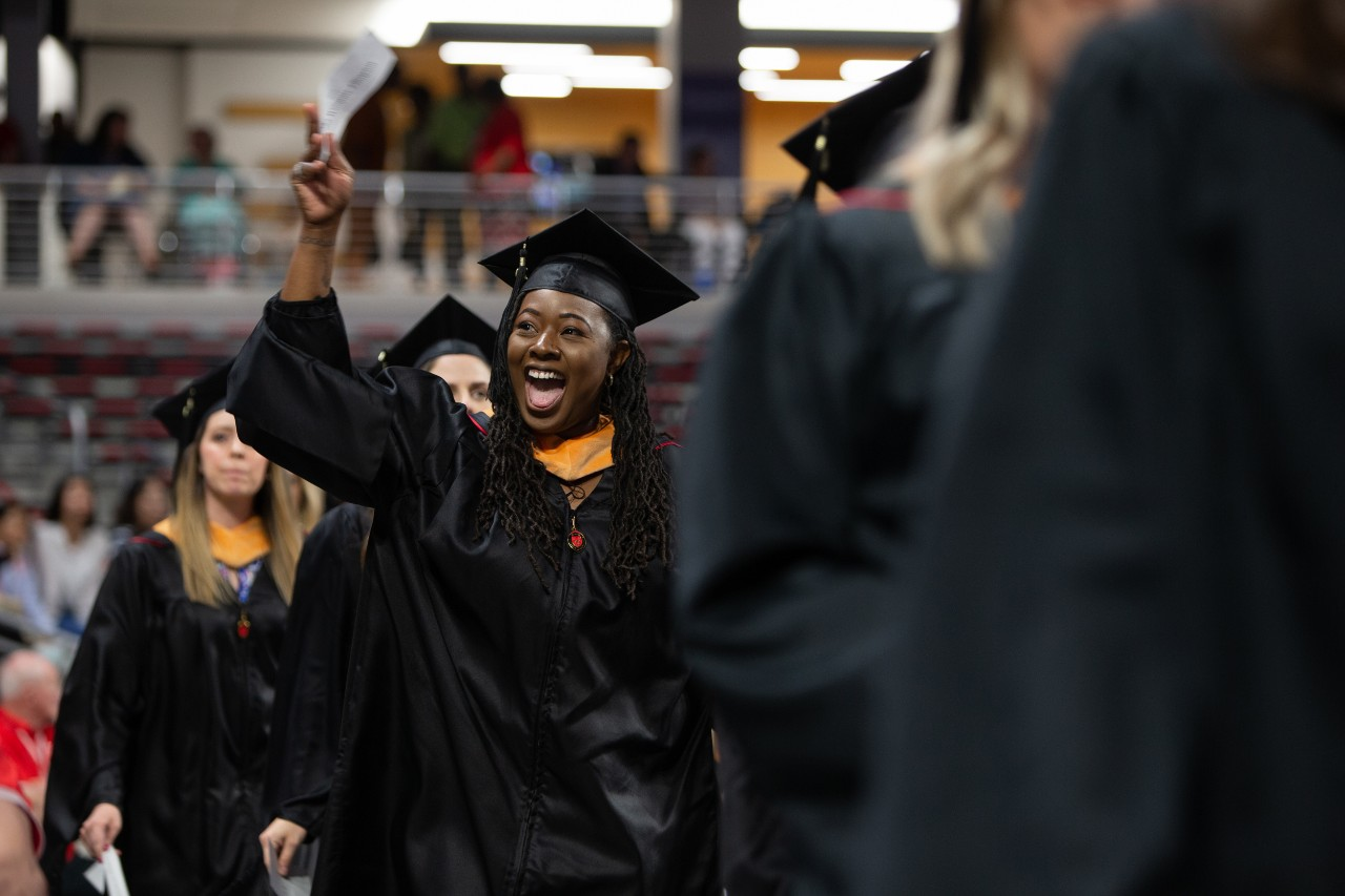 A student in her cap and gown cheers during commencement at Fifth Third Arena.