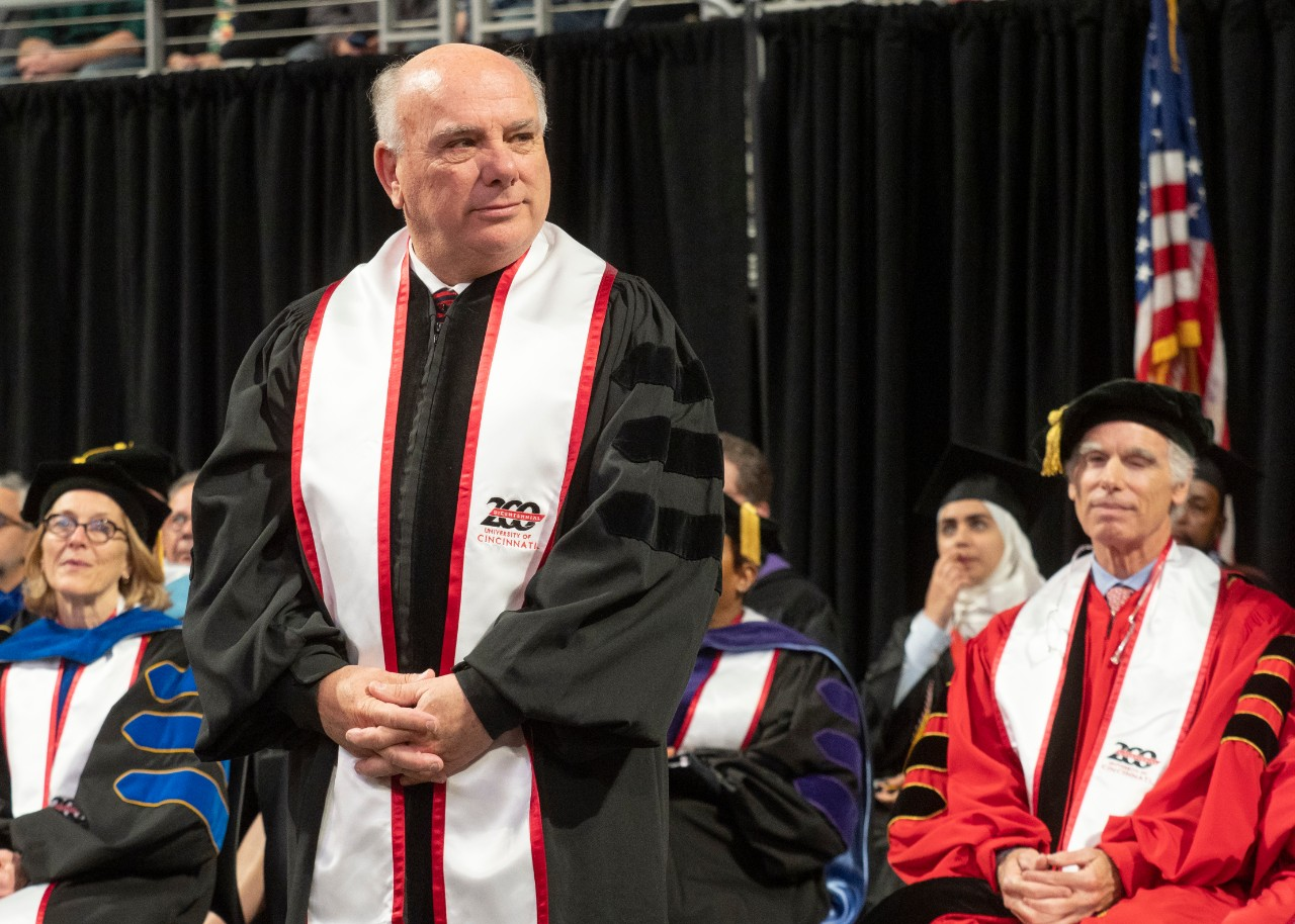 Thomas Cassady stands on stage in a ceremonial gown during commencement.