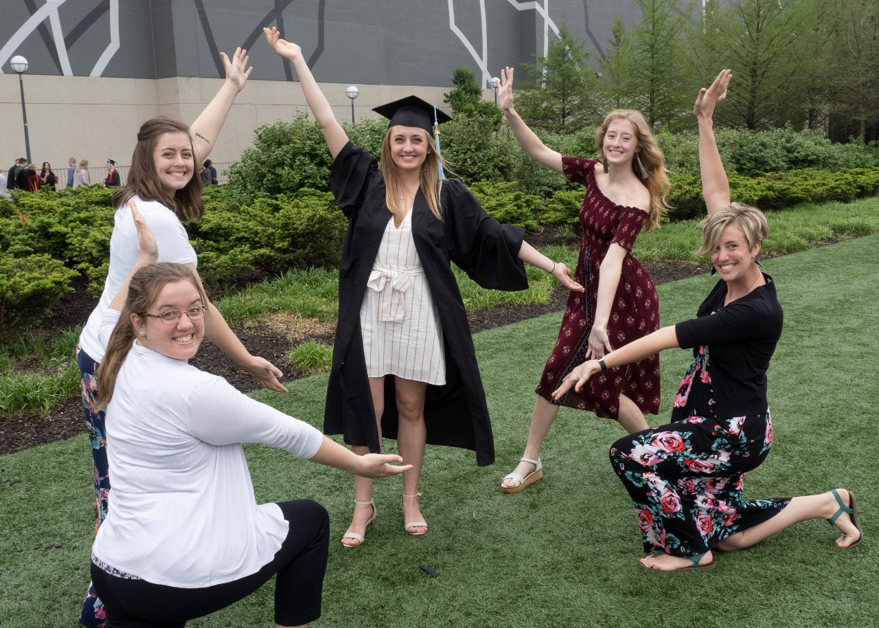 Five women surround their sister to pay tribute to her during commencement.