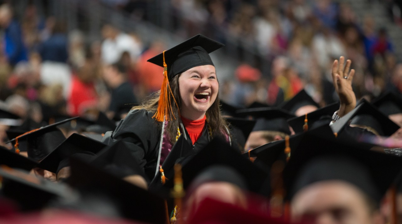 A UC student laughs during commencement.