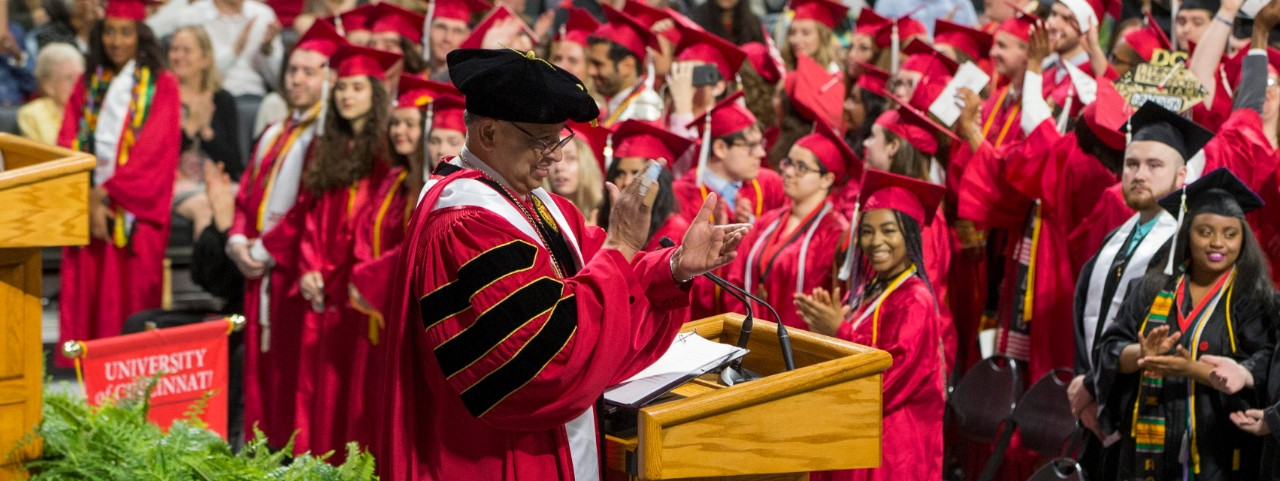 Neville Pinto in a cap and gown applauds on stage with a sea of students in red gowns in front of him.