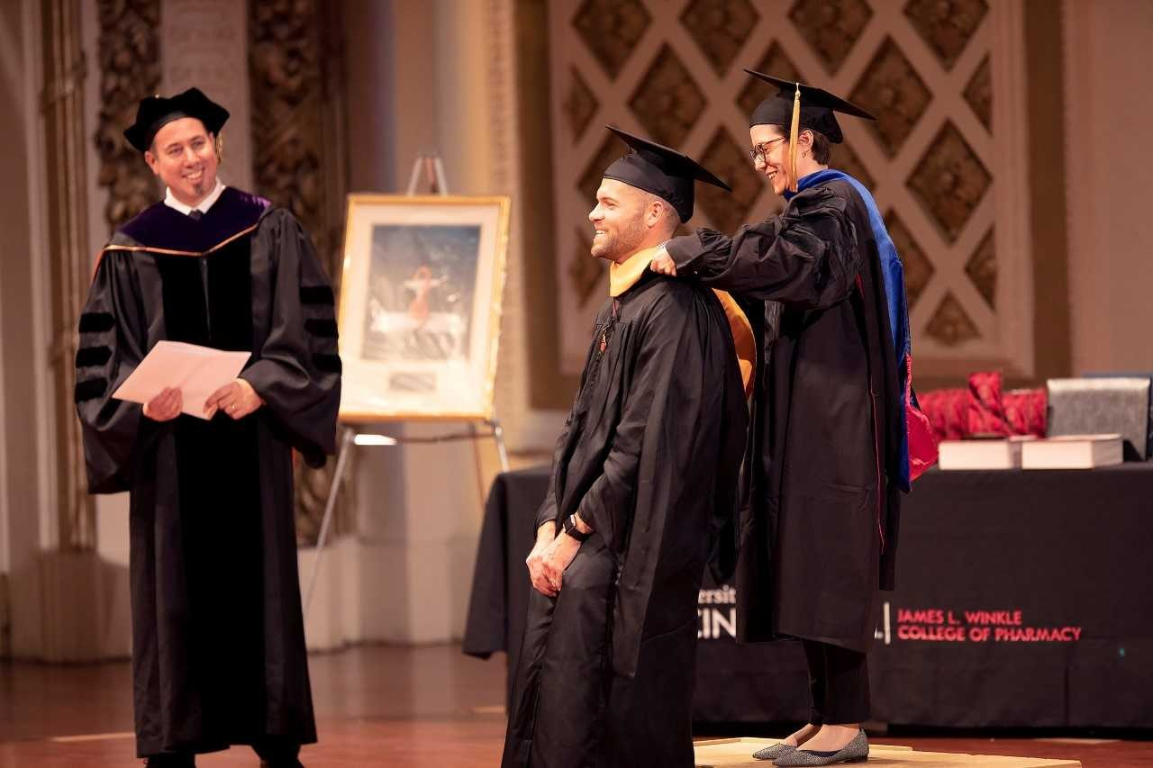 A student smiles while being hooded by a professor while the dean looks on.