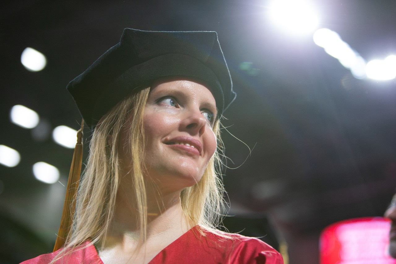 A close portrait of a student smiling under the floor lights of UC's Fifth Third Arena.