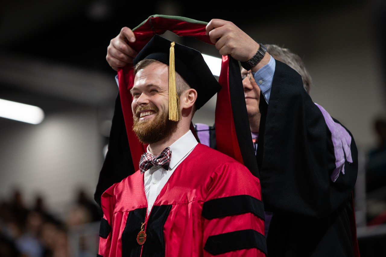 A doctoral student is hooded during UC's commencement.
