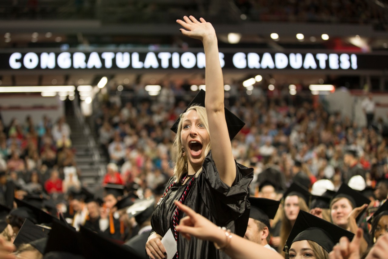 A student in the crowd gives supporters a thumbs up while smiling in her cap and gown.