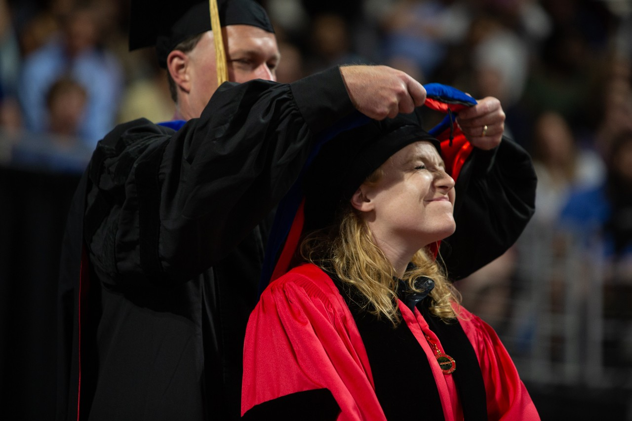 A student closes her eyes while a professor places a ceremonial hood onto her shoulders.