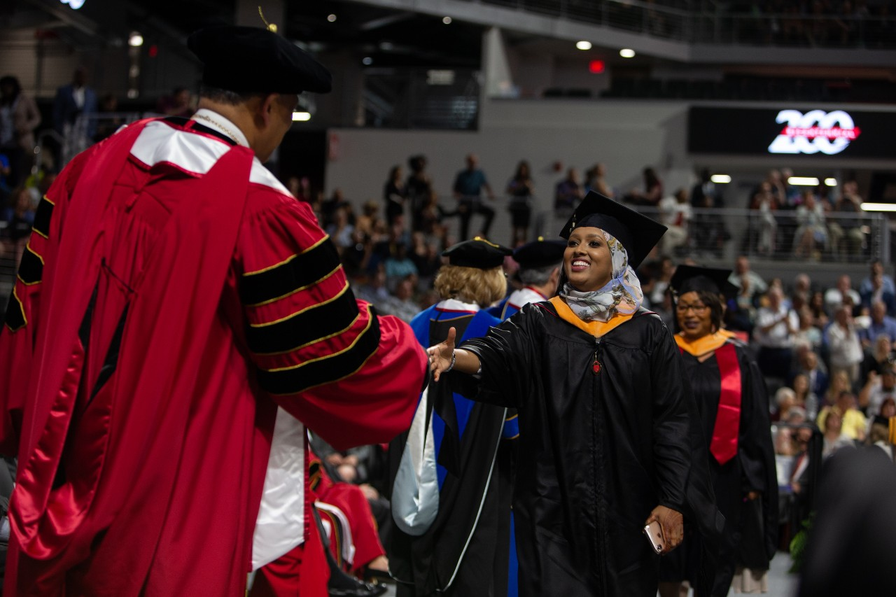 A beaming student shakes hands with the university president on stage at Fifth Third Arena.