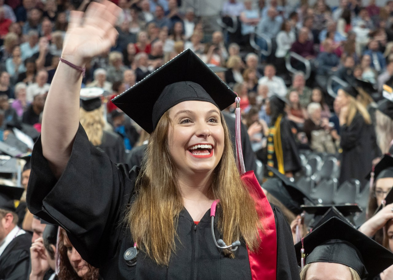 A graduate waves to supporters.