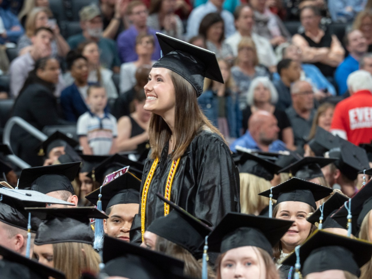 A student in a cap and gown smiles during commencement.
