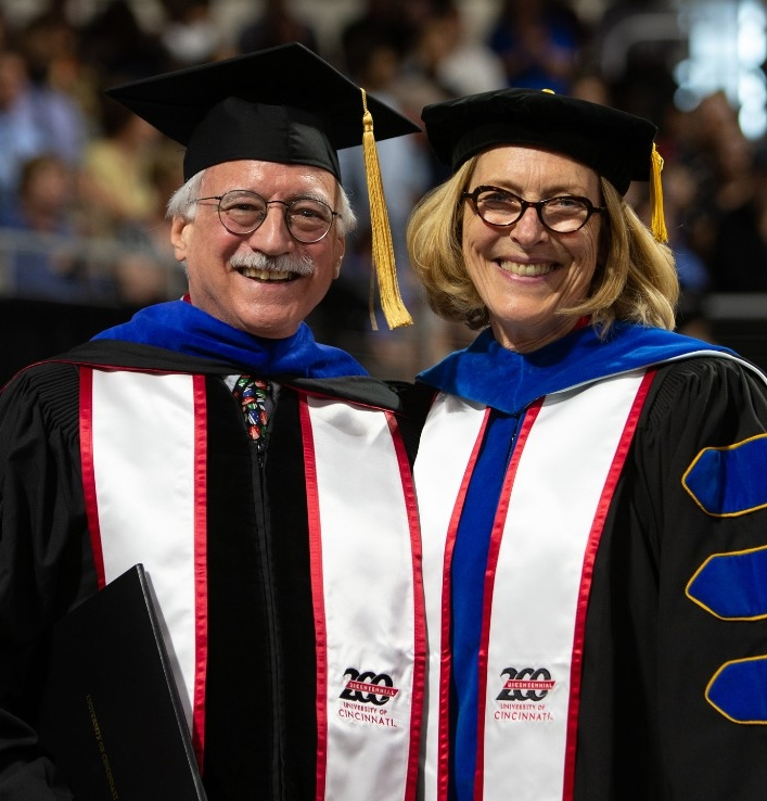 John Drury stands next to Kristi A. Nelson on stage smiling in caps and gowns.