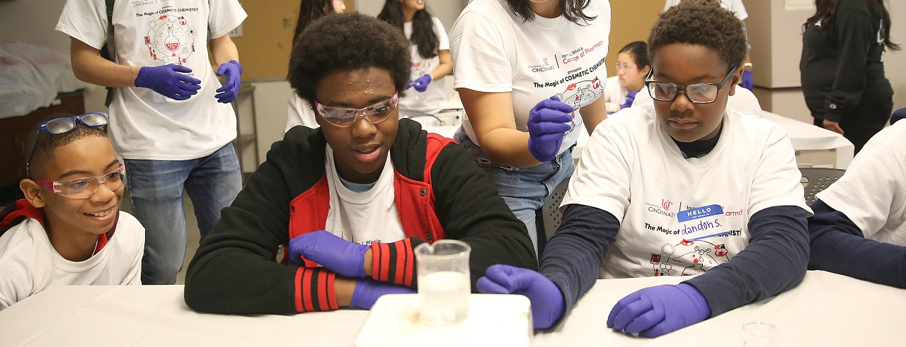 Three young high school students are in a lab, wearing goggles and watching as a chemical compound fizzes in a glass beaker.