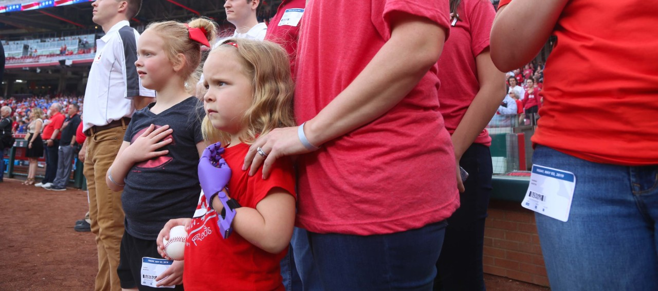 Ella morton holds her prosthetic hand over her heart during the National Anthem at Great American Ball Park.