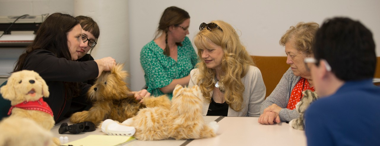 Students, teachers and seniors interact with a robotic cat and dog