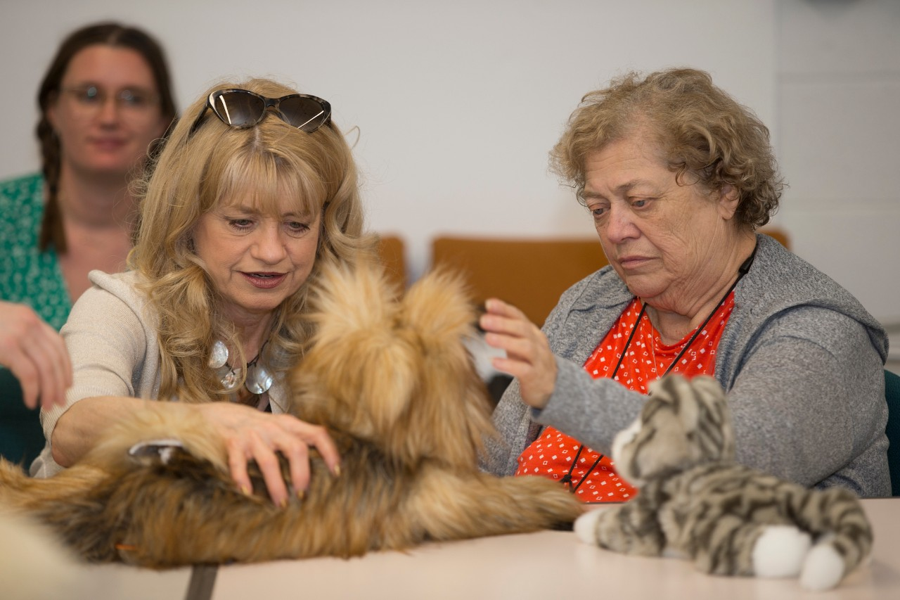 Two older adults interact with a robotic dog and cat