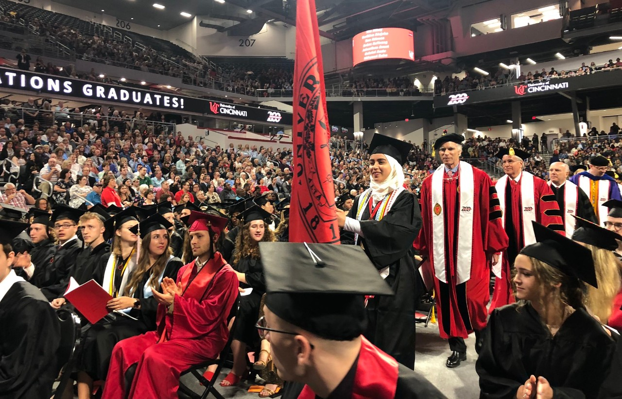Mariam Elgafy carries the flag at the opening of UC's 2019 spring Commencement ceremonies.