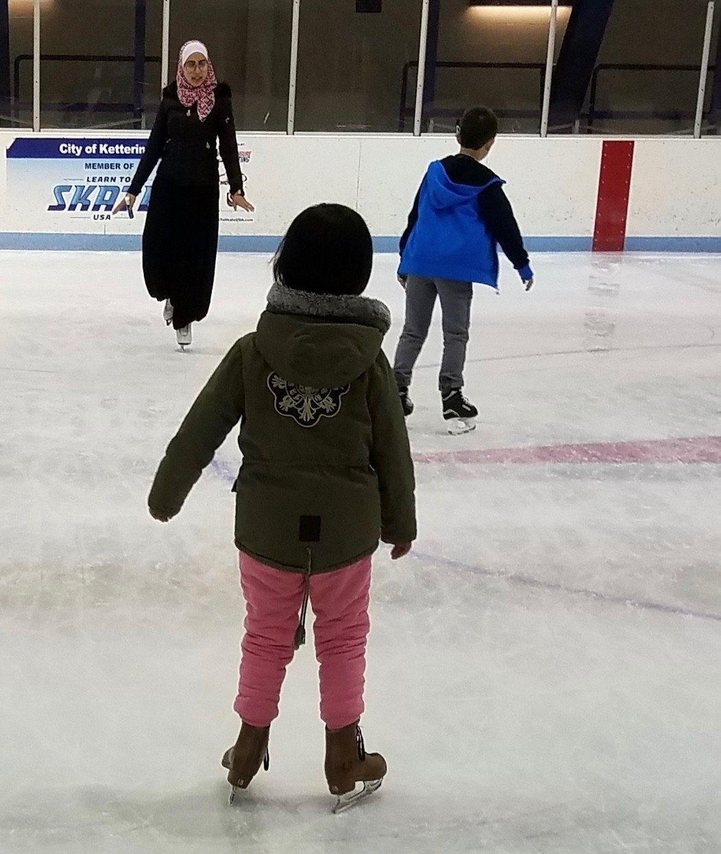 Mariam Elgafy stands on the ice in a skating area teaching young children figure skating.