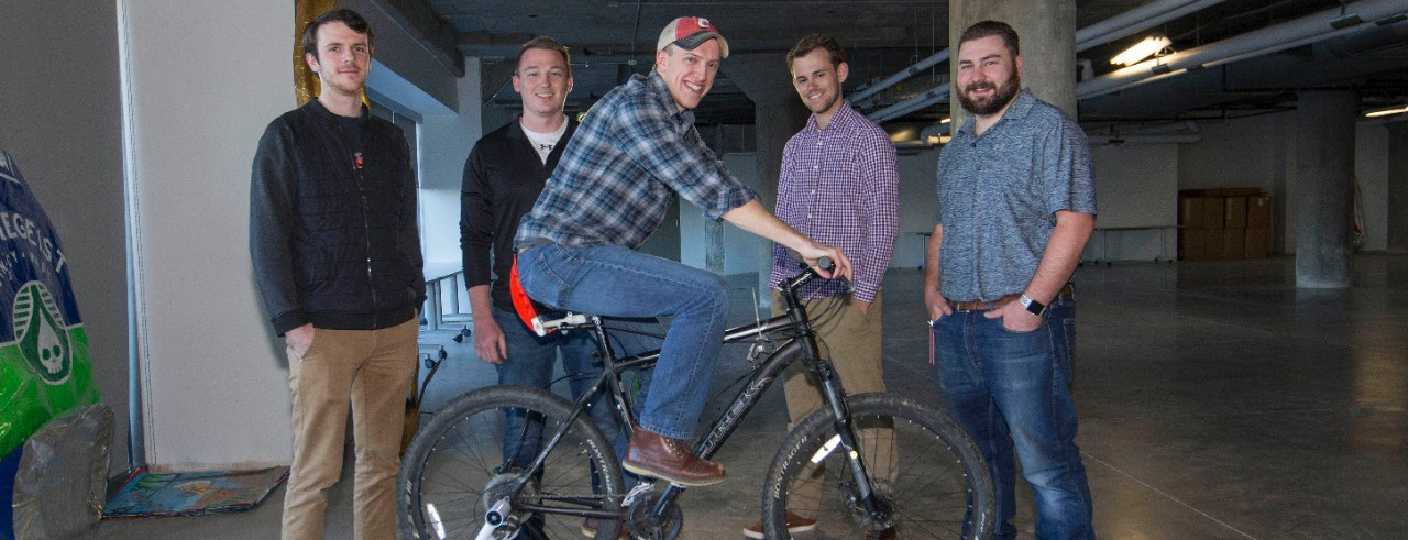 UC mechanical engineers stand around a rider who is testing a new brake on a bicycle mounted on a stationary rack.