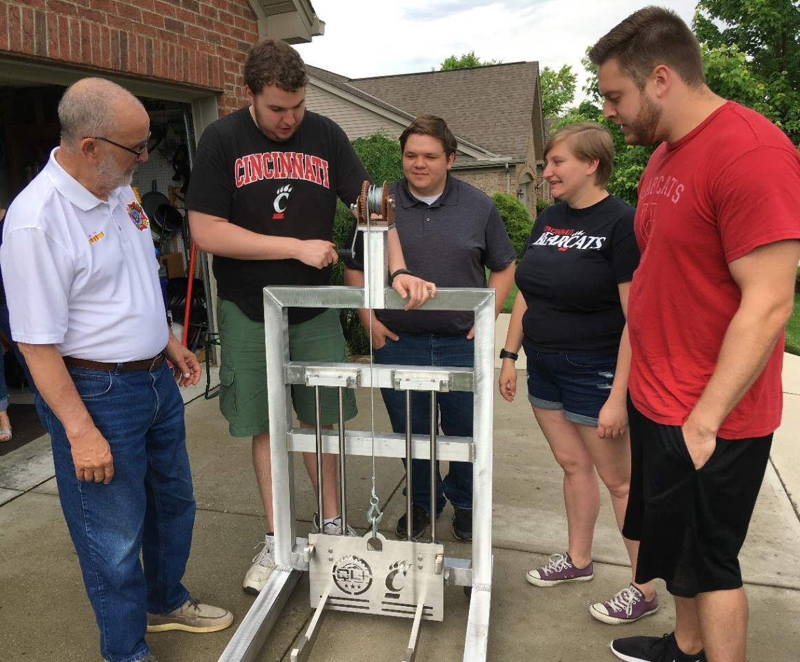 UC students explain the features of the lift to veteran Mike Donnelly in his driveway.