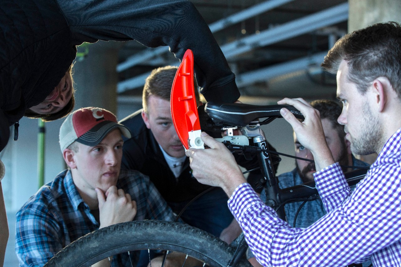 Students huddle around a bicycle while making final adjustments in their custom brake.