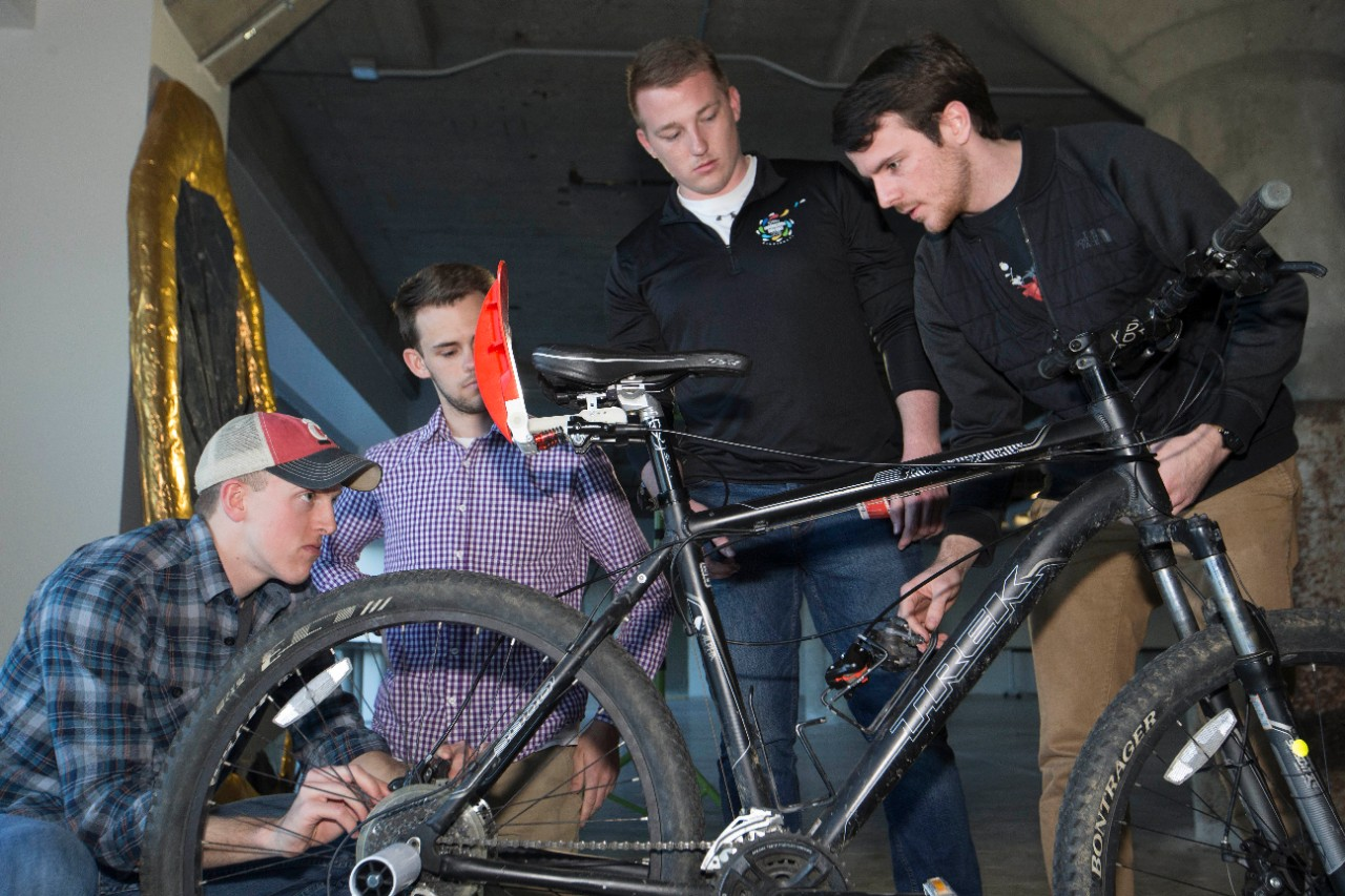UC students huddle around a bicycle making final adjustments to a custom brake operated by a paddle behind the seat.