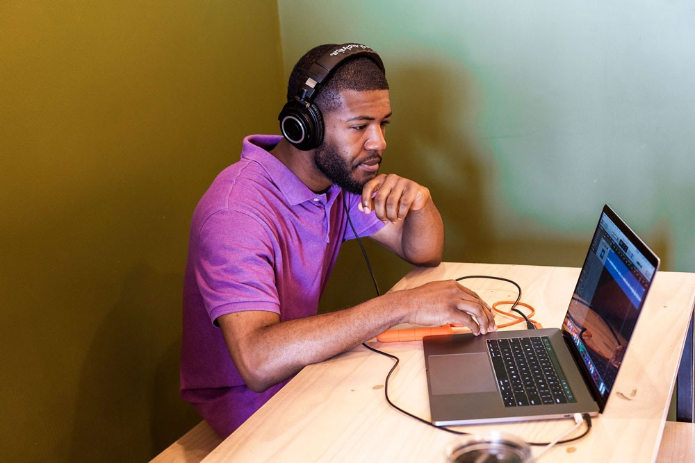A young man wearing headphones and a purple collared shirt works from a laptop