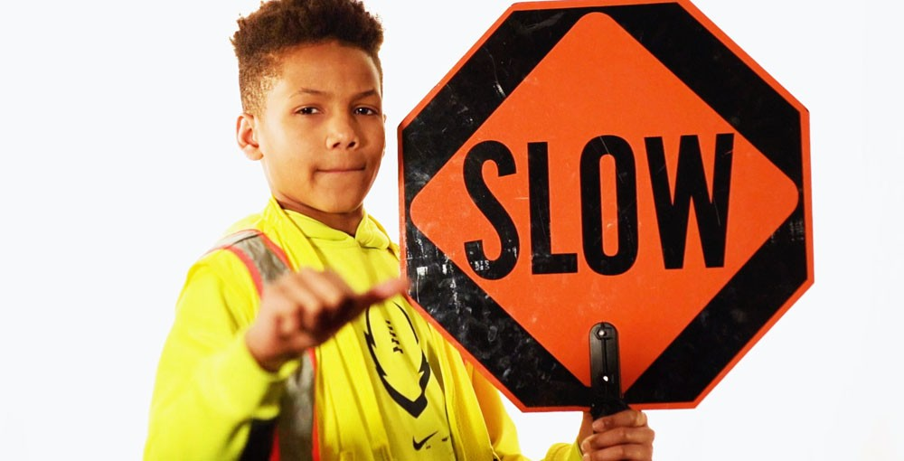 """Young boy in bright yellow jacket with reflective and orange stripes holds and points to an orange sign that says """"SLOW"""" in black letters"""