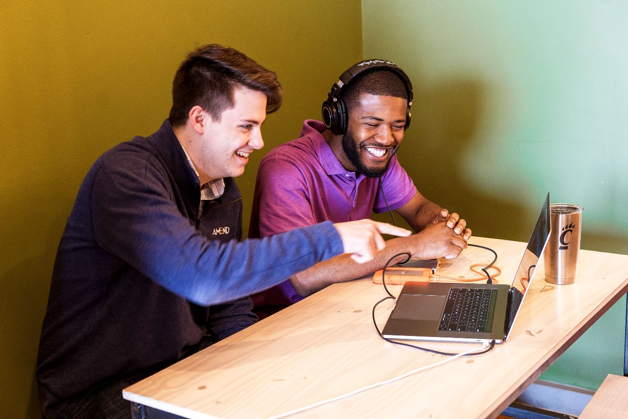 A young man in a navy blue sweater sits next to a young man in a purple collared shirt wearing headphones and look at the same laptop screen