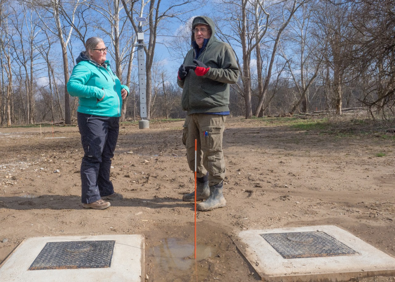Two professors stand in the background in front of two large concrete pads that make up wellheads.