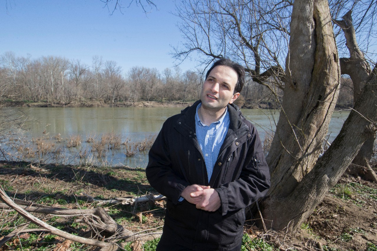 Reza Soltanian stands next to a tree with his hands folded in front of him with the muddy river behind him.