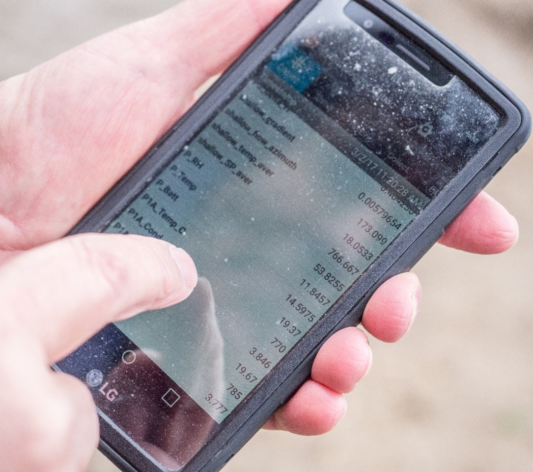 A hand scrolls over a phone screen with data points.