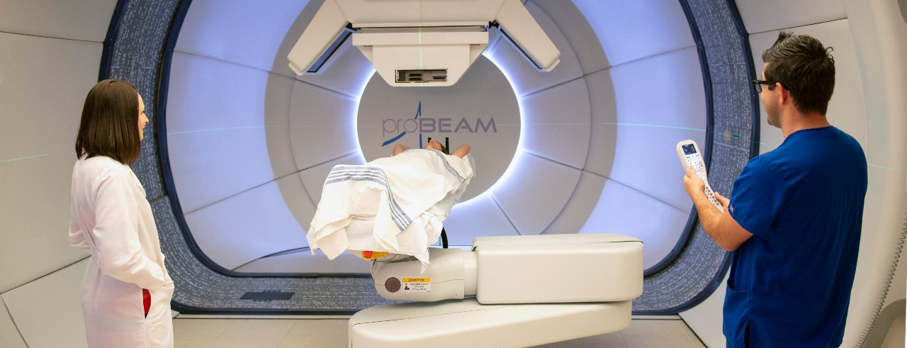 Teresa Meier and radiation therapist with patient in proton therapy gantry